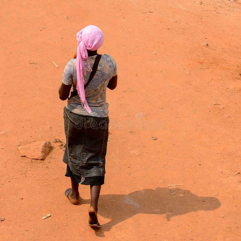 Nicht identifizierte ghanaische Frau von hinten Wege entlang der Straße herein stockbild