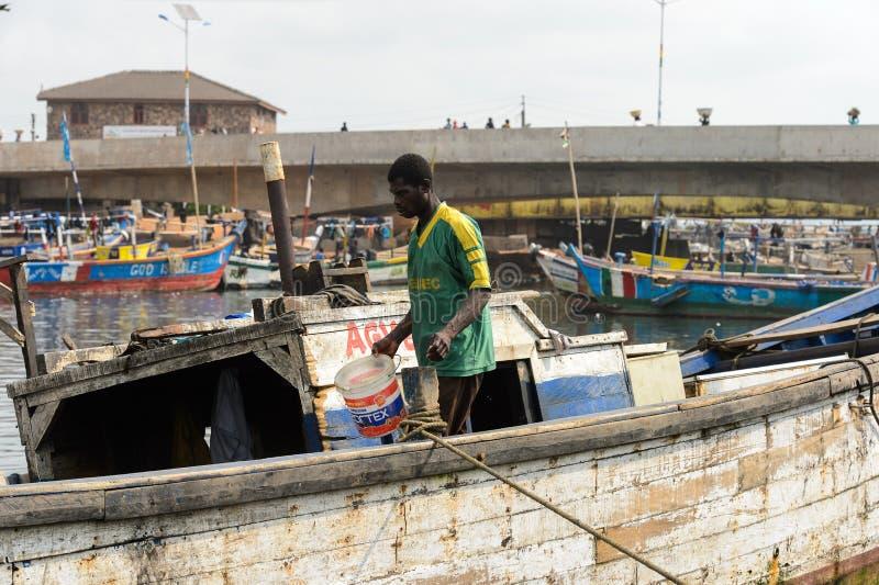 Nicht identifizierte ghanaische Wege im Boot mit einem Eimer in Elmina-por lizenzfreies stockbild