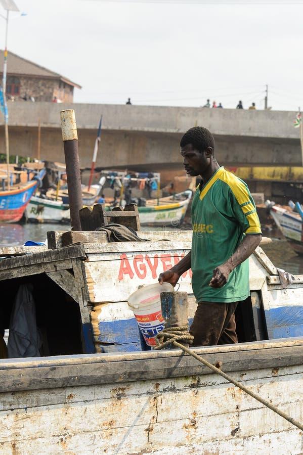 Nicht identifizierte ghanaische Wege im Boot mit einem Eimer in Elmina-por stockfotografie