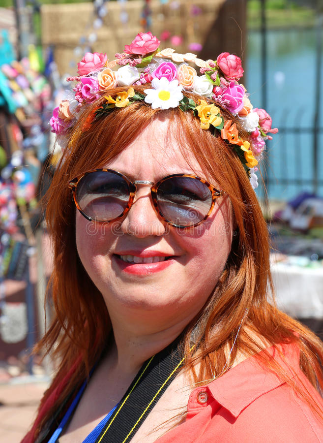 Nicht identifizierte hübsche Frau mit dem Lächeln und Sonnenbrille, die am orange Blüten-Karneval aufwerfen stockfotos
