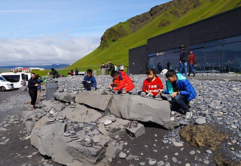 Nicht identifizierte Kinder, die mit Stein nahe Reynisdrangar-Strand, Island spielen lizenzfreies stockfoto