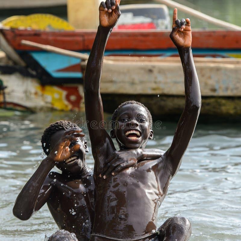 Nicht identifizierte lokale Jungen schwimmen im Wasser während einer Flut lizenzfreies stockfoto