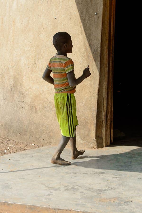 Nicht identifizierter ghanaischer Junge von hinten Wege nahe dem Haus in t stockfotos