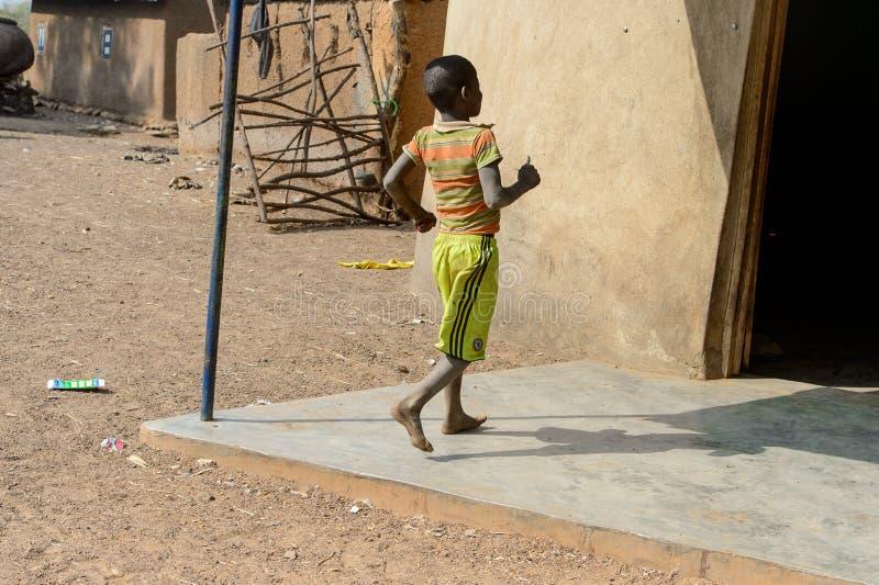 Nicht identifizierter ghanaischer Junge von hinten Wege nahe dem Haus in t lizenzfreies stockbild