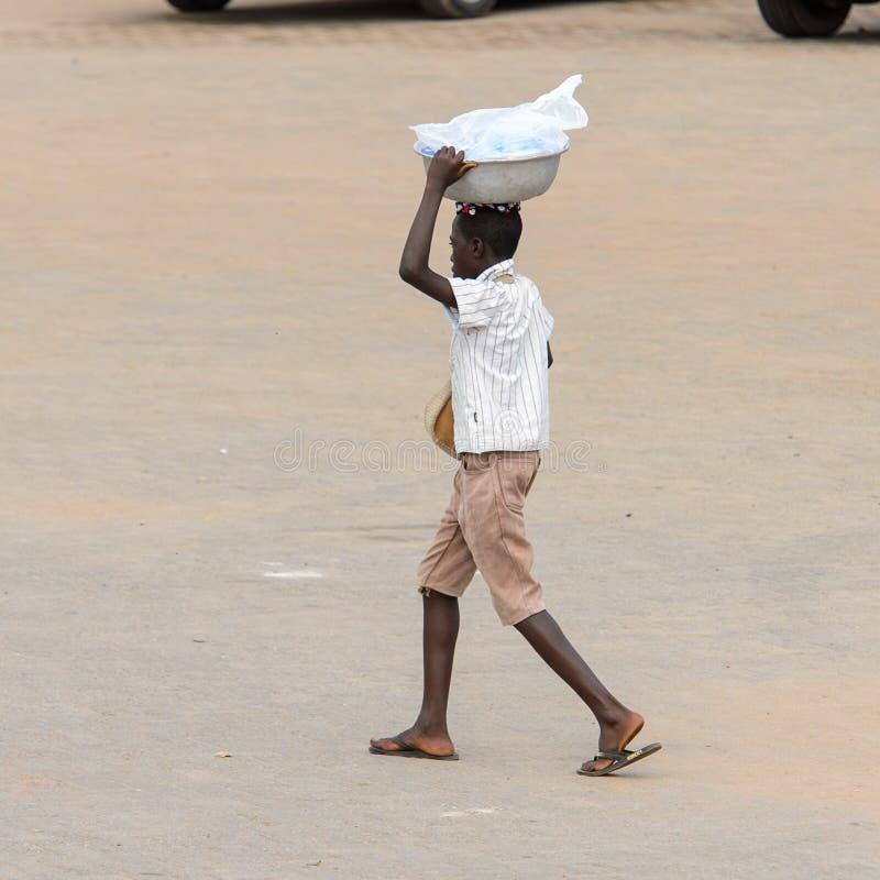 Nicht identifizierter ghanaischer Mann von hinten Wege mit einem Becken auf seinem lizenzfreies stockbild