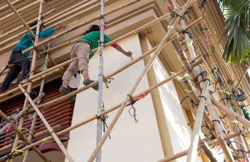 Nicht identifizierter Maler auf dem Baugerüsthandeln erneuern für architec stockbild