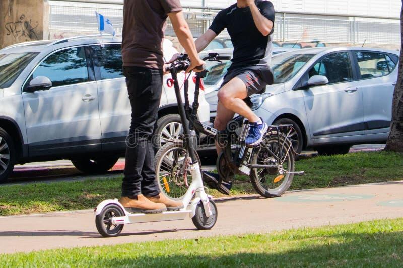 Nicht identifizierter Mann, der einen elektrischen Roller reitet lizenzfreie stockbilder
