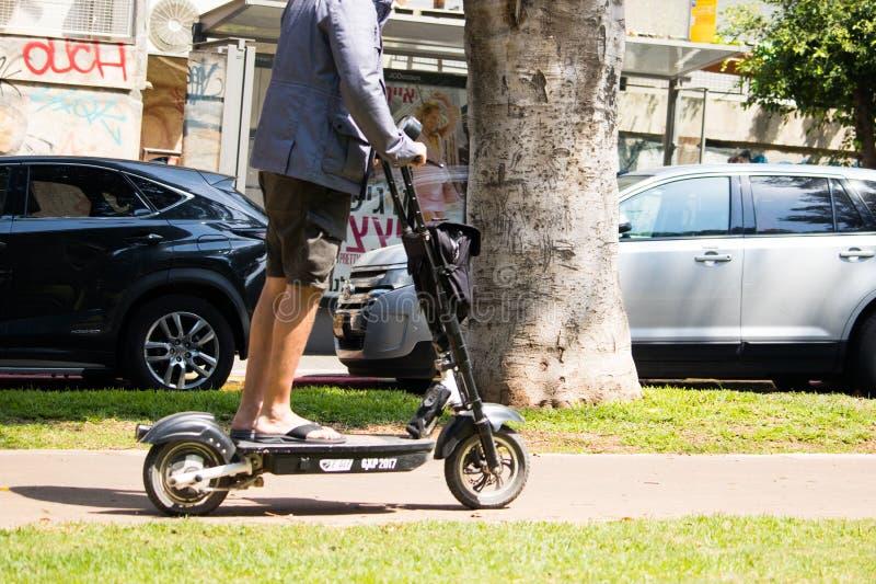 Nicht identifizierter Mann, der einen elektrischen Roller reitet lizenzfreies stockfoto