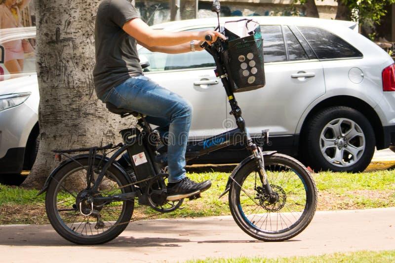 Nicht identifizierter Mann, der elektrisches Fahrrad fährt lizenzfreie stockfotografie
