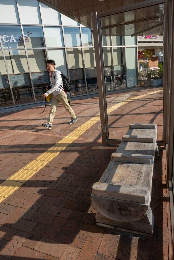 Nicht identifizierter Mann geht durch eine Bank, die vom Kiefernholz am Himeji-Busbahnhof, Japan gemacht wird lizenzfreie stockbilder