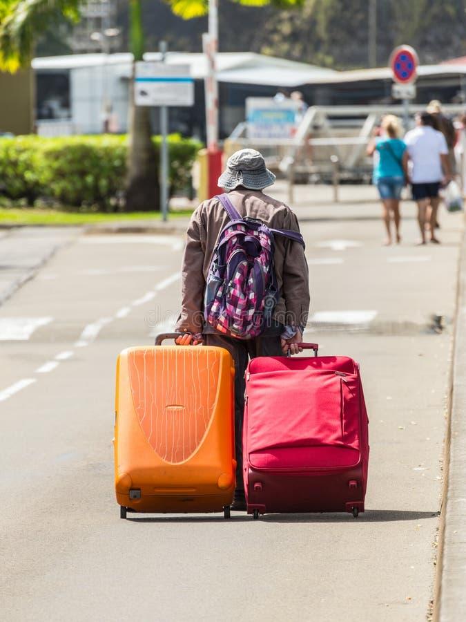 Nicht identifizierter Reisender, der mit zwei Koffern geht lizenzfreie stockbilder