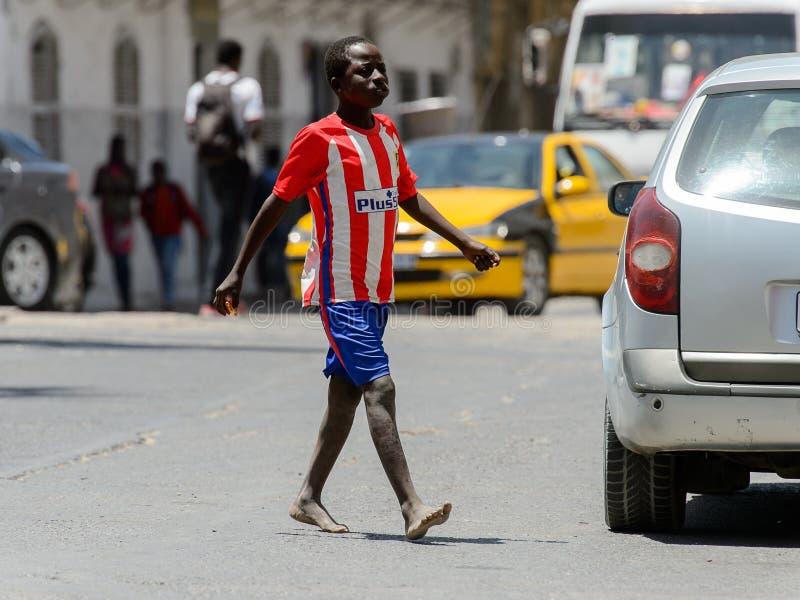 Nicht identifizierter senegalesischer Junge in gestreiftem Hemd geht über das r stockfotografie