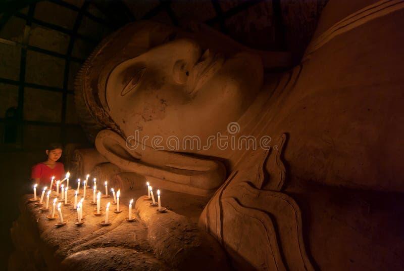 Nicht identifiziertes birmanisches Mädchen, das mit Kerzenlicht in einem Buddihist-Tempel am 5. Januar 2011 in Bagan betet stockbild