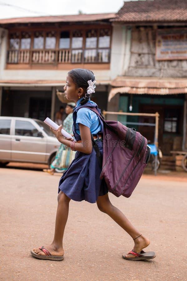 Nicht identifiziertes indisches Mädchen mit einer schweren Schultasche gehen zur Schule lizenzfreies stockbild