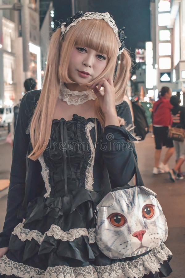 Nicht identifiziertes japanisches Mädchen mit dem blonden Tauchhaar mit einer katzenähnlichen Handtasche bei Harajuku in Beispiel lizenzfreies stockbild
