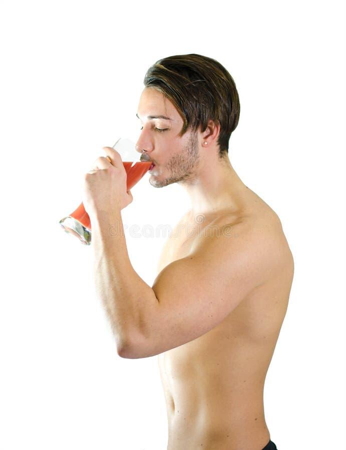 Nicht mehr Bier! Hemdloser trinkender Fruchtsaft des jungen Mannes vom großen Glas lizenzfreies stockfoto