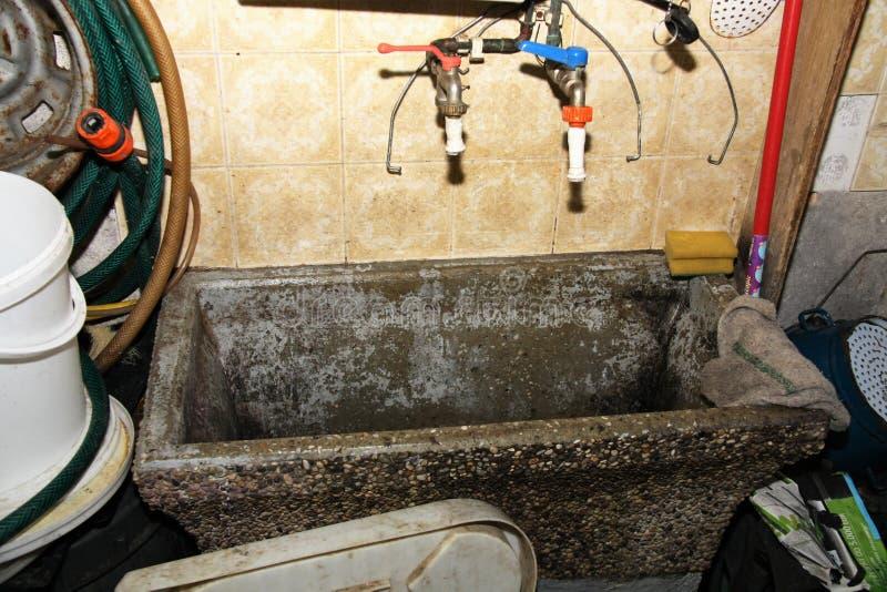 Nicht unordentliches aber verwendbares Reinigungsbecken im Weinkeller stockfotografie