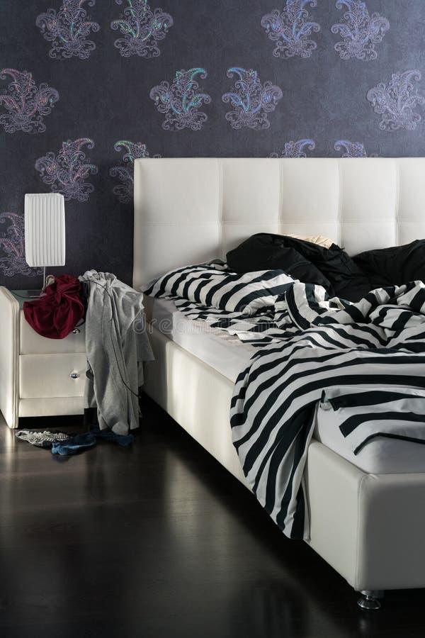 Nicht verstautes Bett und Nachttisch mit Kleidung Verwirren Sie im Schlafzimmer, die Ecke des Betts lizenzfreie stockbilder