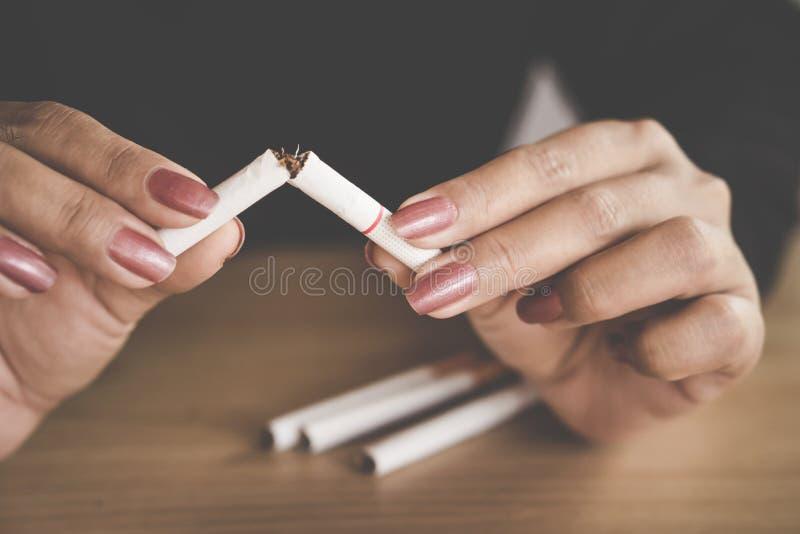 Nichtrauchertag mit der Frauenhand, die Zigarette zerquetscht stockfotografie