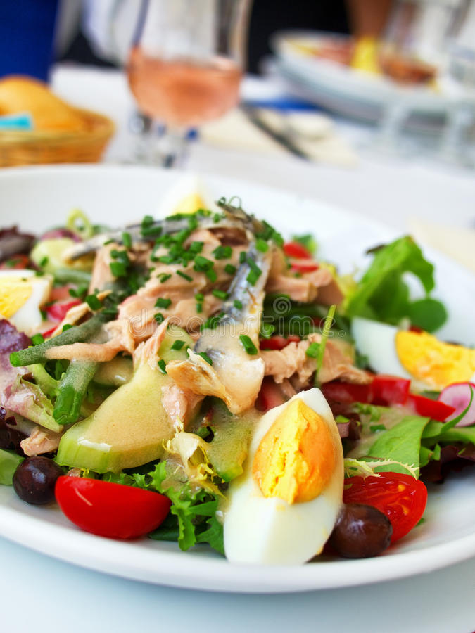Nicoise Salad. Served in a restaurant in Cannes, France. Vertical shot royalty free stock photography