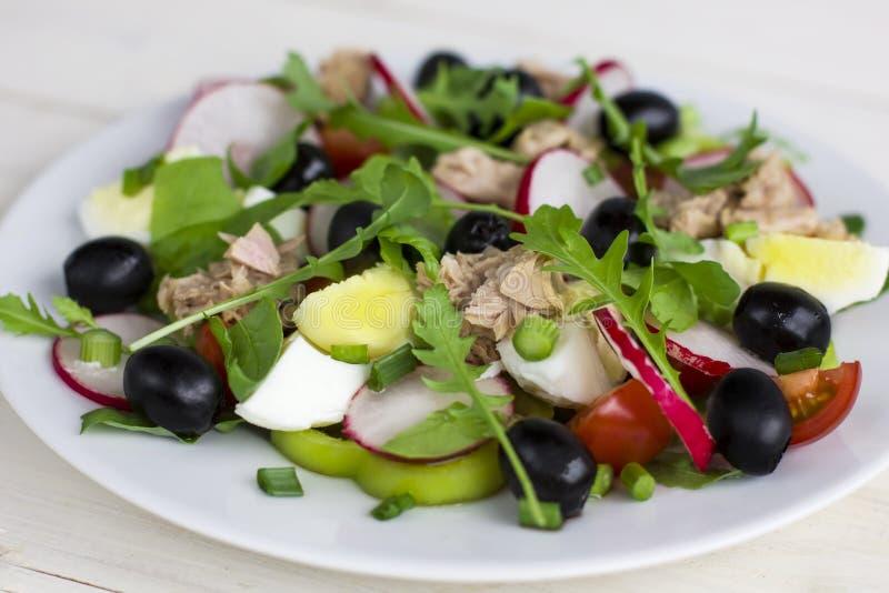 Nicoise sallad med tonfisk, ägget, körsbärsröda tomater och svarta oliv arkivfoto