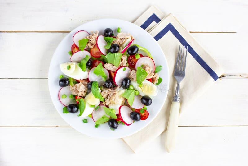 Nicoise sallad med tonfisk, ägget, körsbärsröda tomater och svarta oliv royaltyfri fotografi