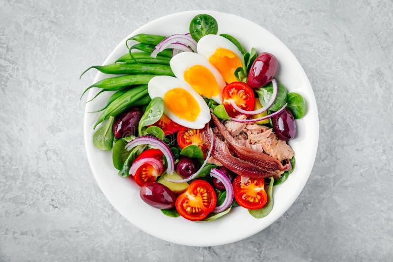 Nicoise sallad med tonfisk, ansjovisar, ägg, haricot vert, oliv, tomater, röda lökar och salladsidor arkivfoton