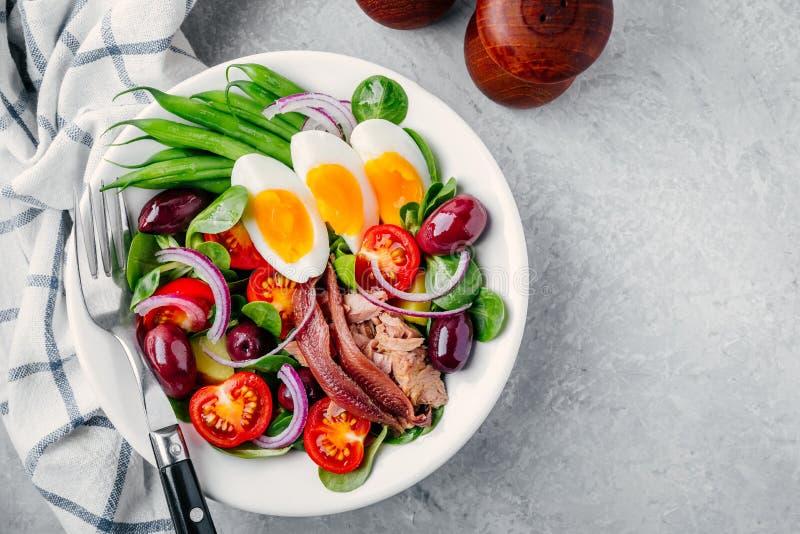 Nicoise sallad med tonfisk, ansjovisar, ägg, haricot vert, oliv, tomater, röda lökar och salladsidor arkivbild