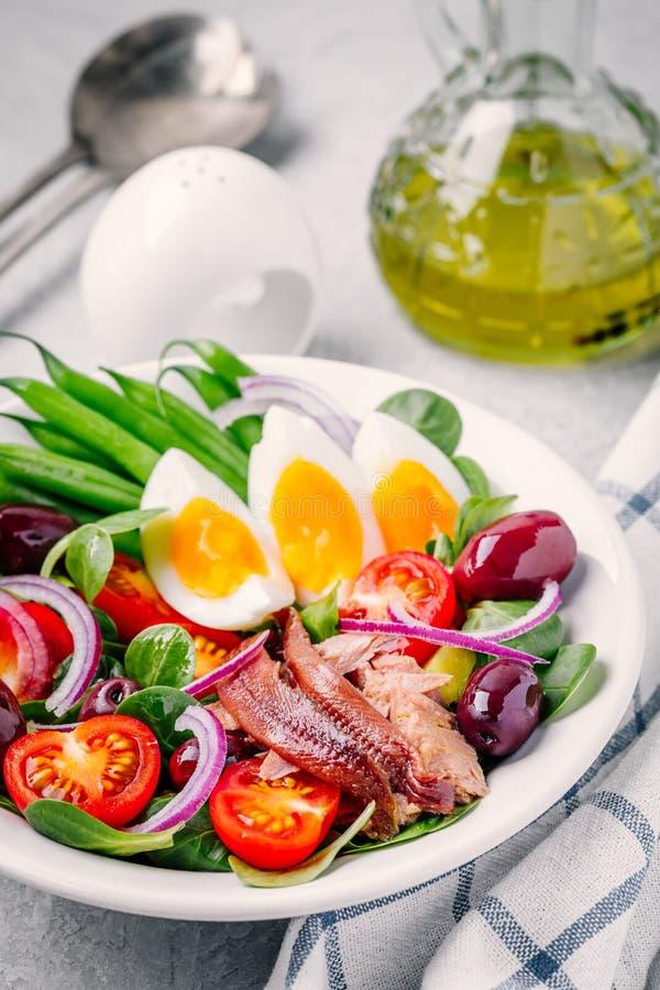 Nicoise sallad med tonfisk, ansjovisar, ägg, haricot vert, oliv, tomater, röda lökar och salladsidor royaltyfri bild