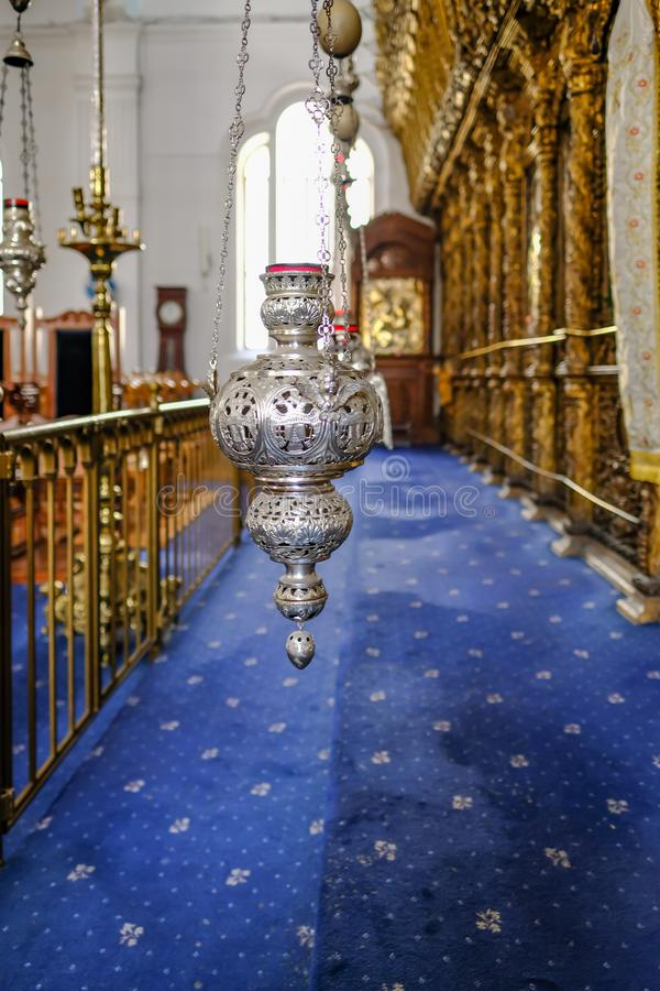 Nicosia, Cyprus - May 14, 2018: Silver intricate oil lamp hanging in front of the icons in the Holy Mary Church in Nicosia. Oil stock images