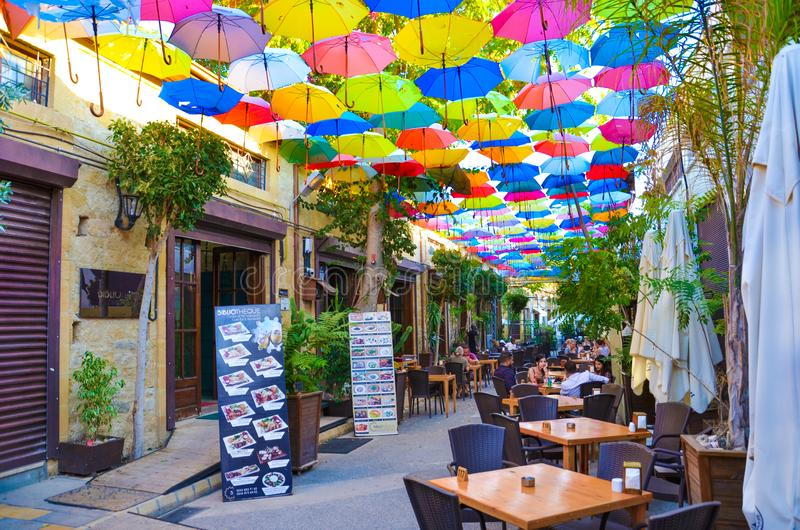 Nicosia, Cyprus - Oct 4th 2018: Outdoor cafe with amazing colorful umbrellas decorating the top of the street stock photography