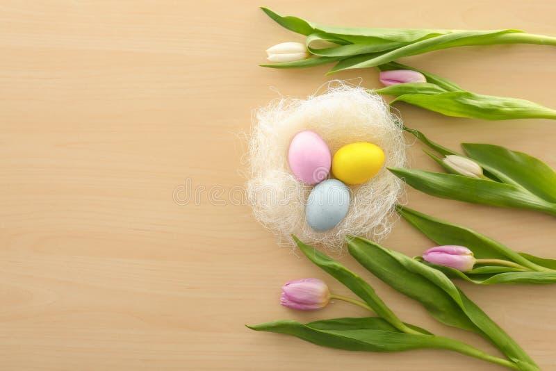 Nid décoratif avec les oeufs de pâques et les fleurs teints de ressort sur la table photo libre de droits