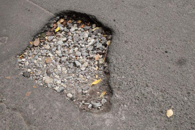 Nid de poule avec le gravier sur la voie urbaine endommagée photo libre de droits