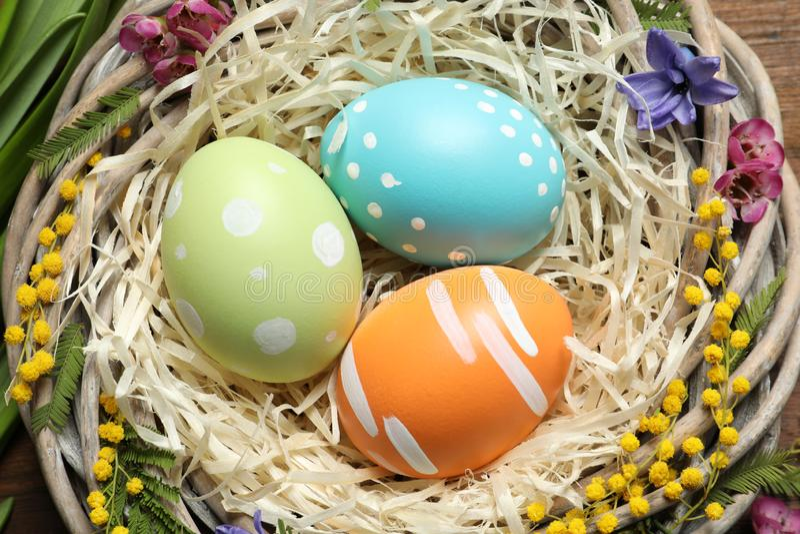 Nid en osier avec les oeufs et les fleurs de pâques peints sur la table images stock