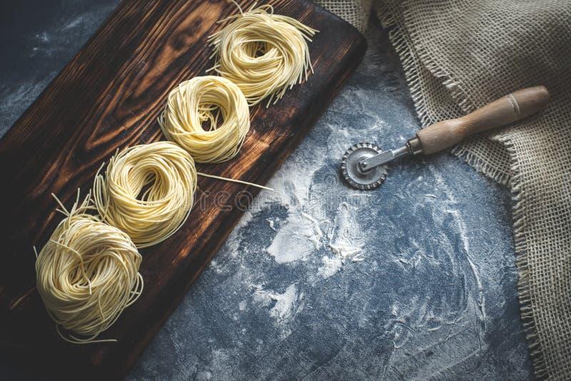 Nids des spaghetti sur un conseil en bois à l'heure de faire cuire les pâtes faites maison images stock