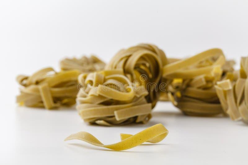 Nids italiens de tagliatelles d'épinards sur le blanc photographie stock libre de droits
