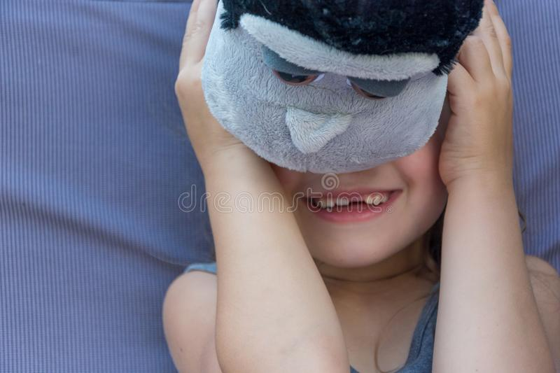 Nieśmiała dziecko dziewczyna chuje jej twarz za zabawką obrazy stock