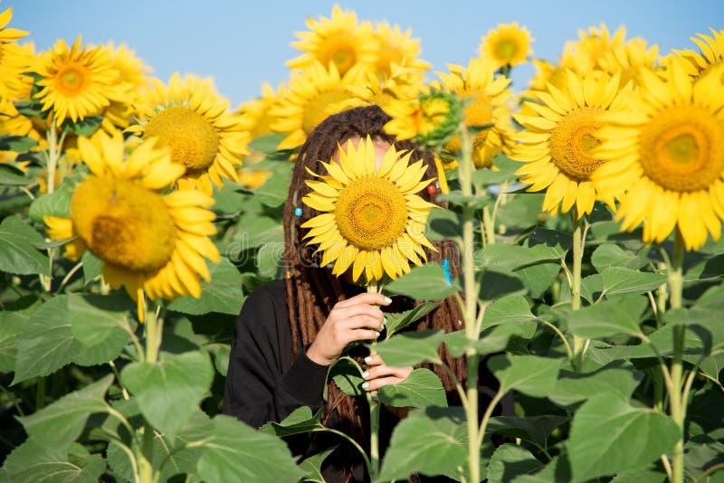 Nieśmiała dziewczyna chował jej twarz za kwiatem słonecznik zdjęcie royalty free
