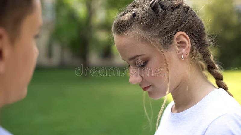 Nieśmiała nastolatek dziewczyna patrzeje w dół, romantyczna data ucznie, niezręczny moment zdjęcie stock