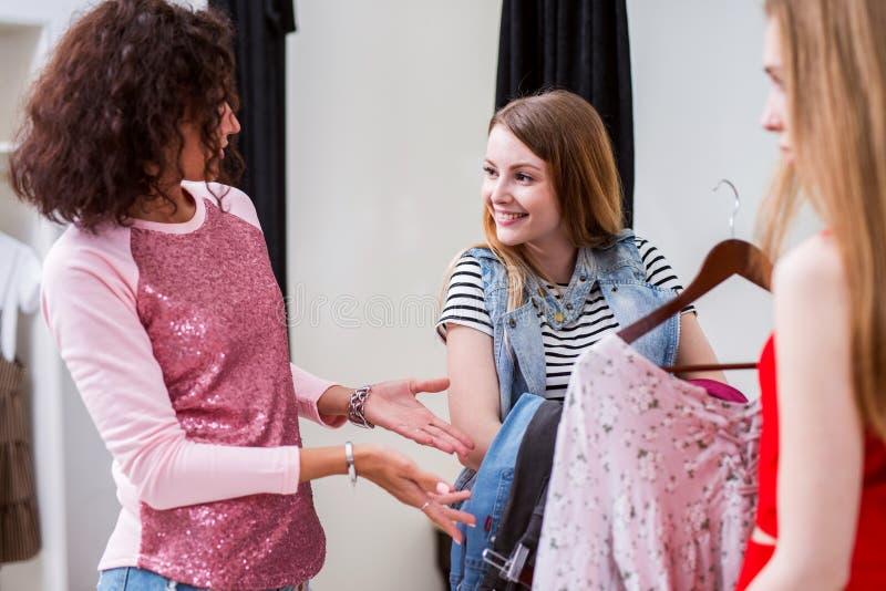 Nieśmiała uśmiechnięta dziewczyna trzyma paczkę odzieżowy słuchanie fasonować stylisty pomaga jej zrywanie strojowi w odmienianie obraz royalty free