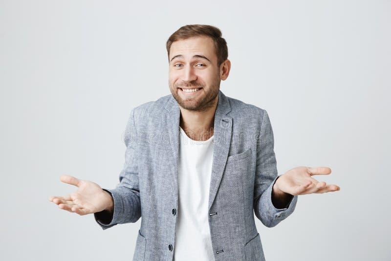Nieświadomy intrygujący atrakcyjny mężczyzna wzrusza ramionami ramion wyrażać z brodą, ono uśmiecha się szeroko, mieć wahanie obraz stock