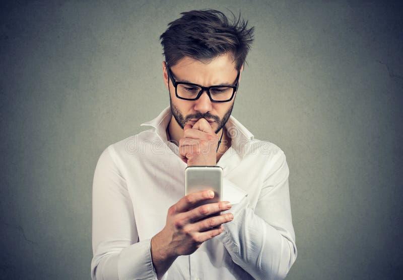Nieświadomy młody człowiek ma kłopoty z jego smartphone zdjęcie stock