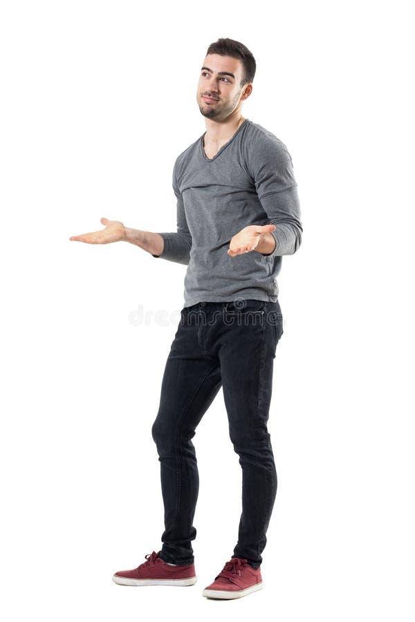 Nieświadomy zmieszany młody człowiek wzrusza ramionami ramiona patrzeje daleko od obrazy stock