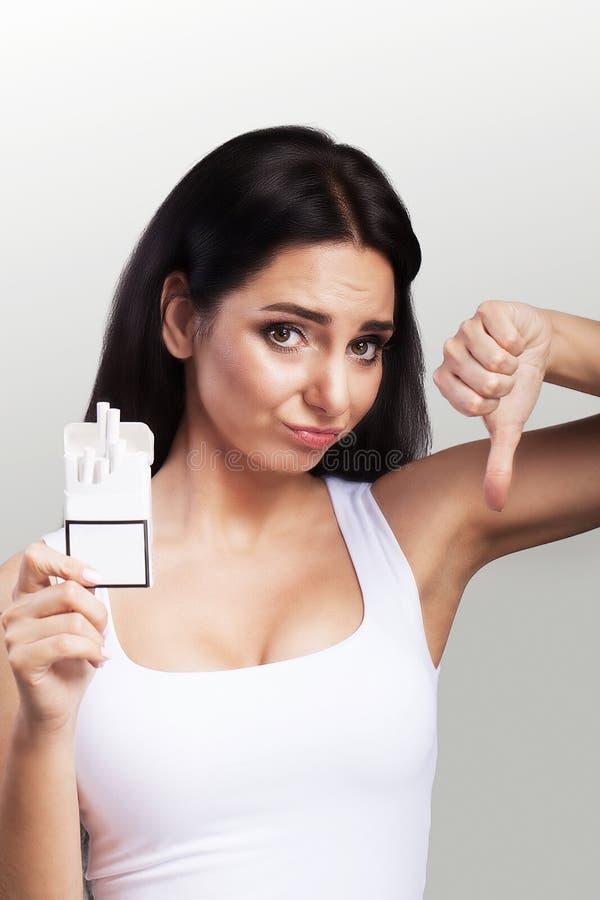 nieżywy palenie zabronione Młoda piękna kobieta agituje przeciw dymieniu Trzyma paczkę w jego rękach gardzi dymienie Pojęcie zdro zdjęcia royalty free