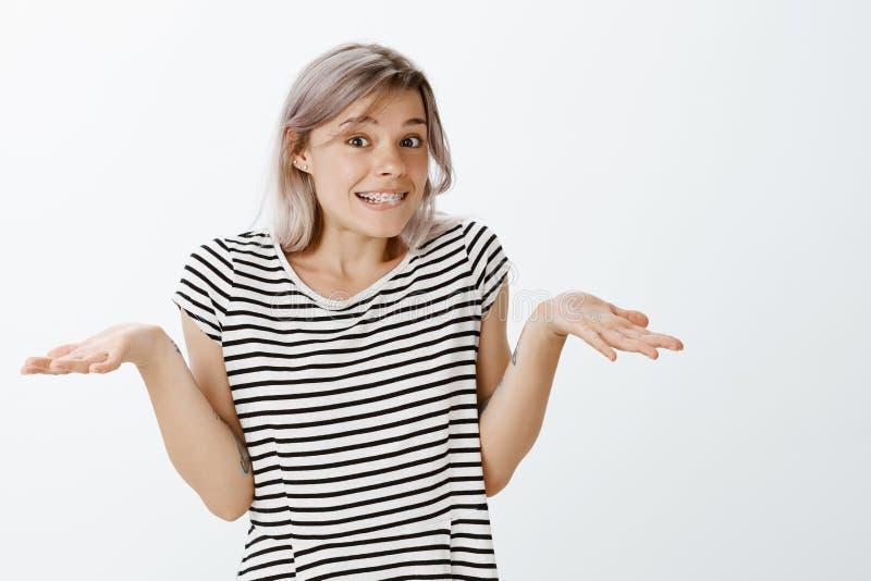 Nie mieć pojęcia naprawdę Beztroska śliczna jasnogłowa młoda kobieta wzrusza ramionami palmy na boku i rozprzestrzenia w pasiaste fotografia stock
