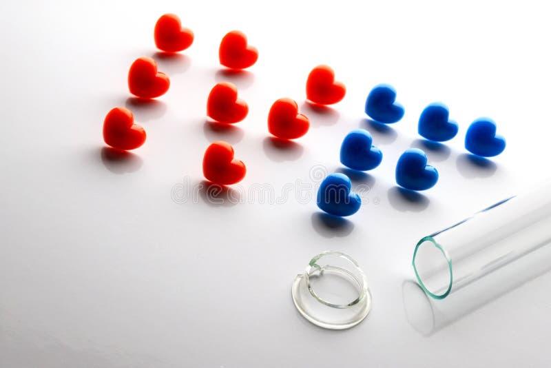 Nie udać się nawożenie in vitro Łamana próbna tubka z rozszczepioną szyją IVF Listy komponowali czerwoni i błękitni serca na biel obrazy royalty free