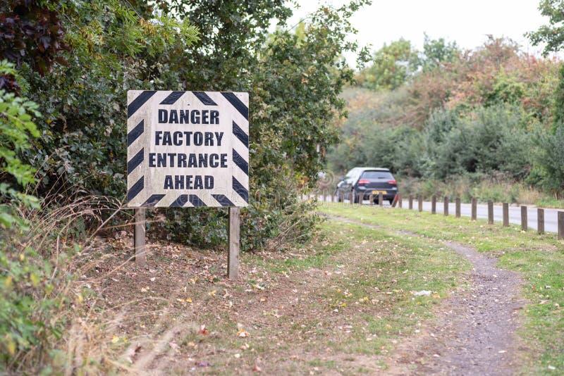 Niebezpieczeństwa Fabryczny wejście Naprzód ostrzega drogowego znaka na Brytyjskim drogowym światło dzienne widoku zdjęcie royalty free