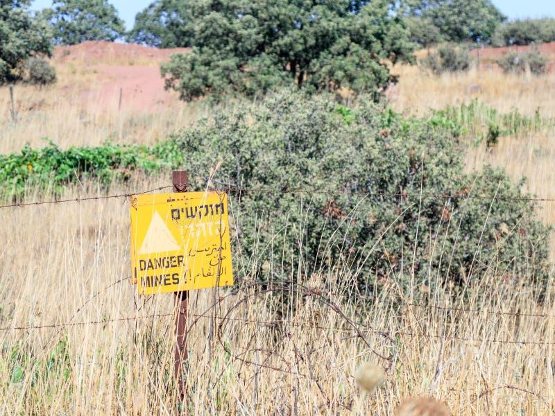 ` niebezpieczeństwa szyldowe czytelnicze kopalnie! ` wiesza od drutu kolczastego ogrodzenia w wzgórze golan, blisko granicy z Syr fotografia stock