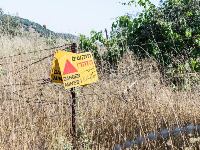 ` niebezpieczeństwa szyldowe czytelnicze kopalnie! ` wiesza od drutu kolczastego ogrodzenia w wzgórze golan, blisko granicy z Syr obraz royalty free