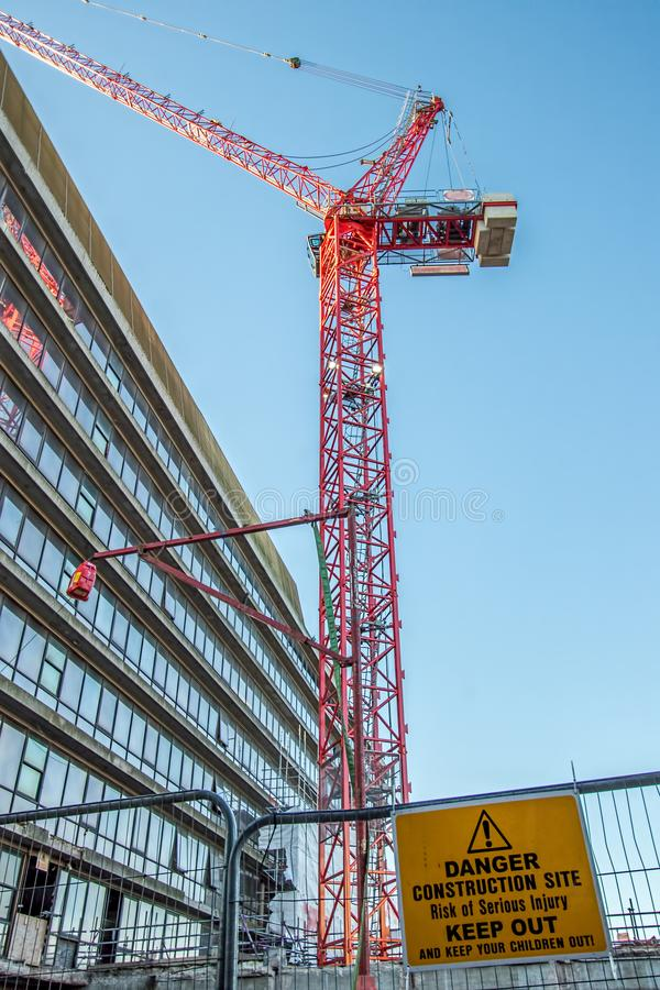 Niebezpieczeństwo budowa utrzymuje out szyldowy z czerwonym żurawiem nad miastem zdjęcia royalty free